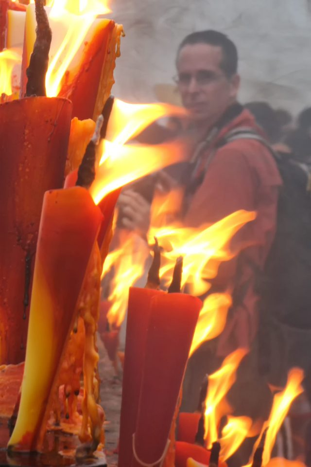 Tony surround by burning candles at the peak of Emei Shan
