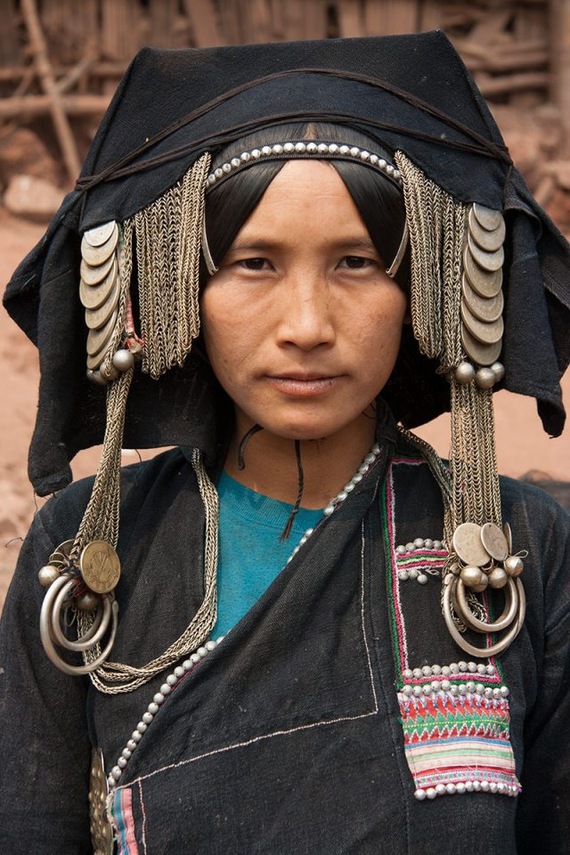 Akha woman wearing headdress full of old coins