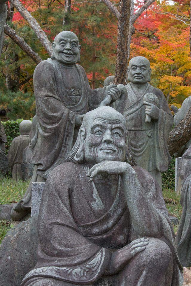 Statues backed by autumn foliage in Arashiyama