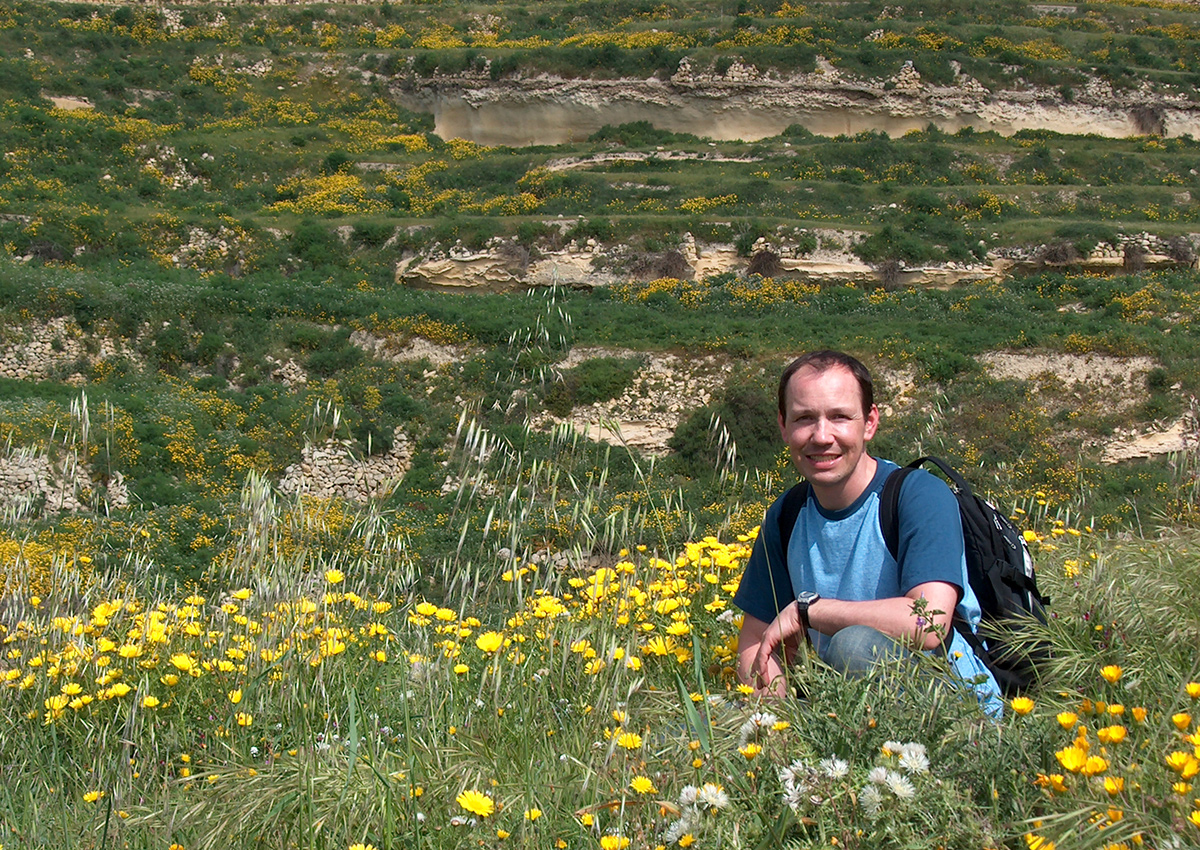 Thomas rests in a field of Gozo flowers
